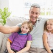 Father taking selfie with children on sofa — Stock Photo #68997125