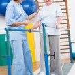 Senior woman walking with parallel bars with therapist  — Stock Photo #68997483