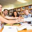 Students placing hands together over library table — Stock Photo #68997787