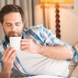 Man relaxing on bed with hot drink — Stock Photo #68997899