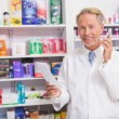 Smiling senior phoning while reading prescription — Stock Photo #68998285