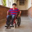 Boy sitting in wheelchair in school corridor — Stock Photo #68999317