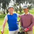 Golfing friends smiling at camera holding clubs — Stock Photo #68999541
