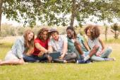 Happy friends in the park looking at tablet — Stockfoto