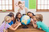 Carino allievi ed insegnante in aula con il globo — Foto Stock