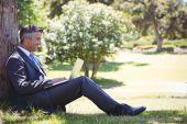 Affärsman med laptop i parken — Stockfoto