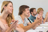 Students clapping hands in classroom — Stock Photo