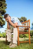 不安的男人坐在公园的长椅上 — 图库照片