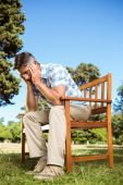 Upset man sitting on park bench — Stock Photo