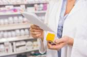 Pharmacist looking at prescription and medicine — Stock Photo