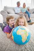 Children exploring globe while parents sitting on sofa — Stock Photo