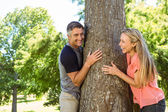 Happy couple hugging a tree — Stock Photo