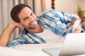 Man relaxing on bed with laptop — Stock Photo