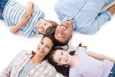Happy parents and children lying on white background — Stock Photo