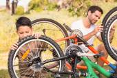Father and son repairing bike together — Stock Photo