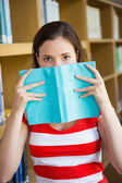 Student covering face with book in library — 图库照片