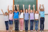 Cute pupils smiling at camera in classroom — Stock Photo