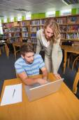 Student getting help from tutor in library — Stock Photo