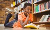 Cute boy reading book in library — Stock Photo