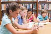 Cute pupil using tablet computer in library — Stock Photo