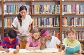 Pretty teacher helping pupils in library  — Stock Photo