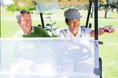 Golfing friends driving in their golf buggy — Foto de Stock