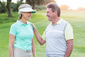Golfing couple smiling at camera on the putting green — Stock Photo