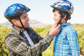 Father attaching his son cycling helmet — Stock Photo
