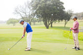Golfer swinging his club with friend behind him — Stock Photo