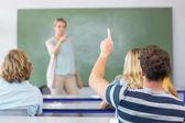 Student raising hand in classroom — Stock Photo