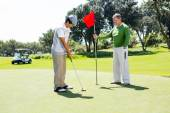 Golfer holding hole flag for friend putting ball — ストック写真