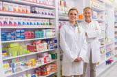 Pharmacist with his trainee standing and smiling at camera — Stock Photo