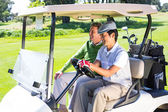 Golfing friends laughing together in their golf buggy — Stock Photo