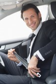Businessman putting on his seat belt — Stock Photo