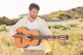 Homem feliz sorrindo para a câmera tocando guitarra — Fotografia Stock