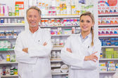 Pharmacist and his trainee with arms crossed — Stock Photo