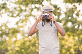 Handsome hipster using vintage camera — Stock Photo
