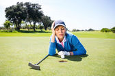 Female golfer looking at her ball on putting green — Stock Photo