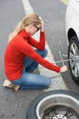 Annoyed woman trying to replace tire — Stock Photo