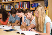 College students doing homework in library — Stock Photo