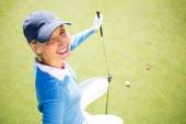 Smiling lady golfer kneeling on the putting green — Stock Photo