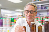 Senior holding and looking at jar of medicine — Stock Photo