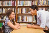 Insegnante femminile e bambina in biblioteca — Foto Stock