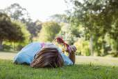Pretty woman lying down in park — Stock Photo