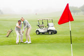 Golfing couple putting ball together — Stock Photo