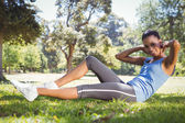 Fit woman doing sit ups in the park — Stock Photo