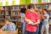 Male college student holding books in library — Stock Photo