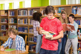 Male college student holding books in library — Stockfoto