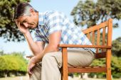 Upset man sitting on park bench — Stock Photo