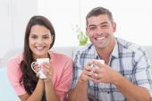 Happy couple holding coffee mugs at home — Stock Photo